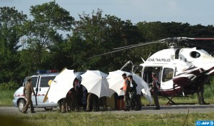 Thai police and military personel use umbrellas to shield a helicopter evacuation at a military airbase in Chiang Rai as operations continue for the 8 boys and their coach trapped in Tham Luang cave in Khun Nam Nang Non Forest Park in the Mae Sai district of Chiang Rai province on July 9, 2018. Four boys among the group of 13 trapped in a flooded Thai cave for more than a fortnight were rescued on July 8 after surviving a treacherous escape, raising hopes elite divers would also save the others soon. / AFP PHOTO / LILLIAN SUWANRUMPHA